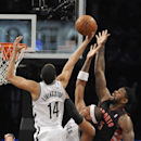 Brooklyn Nets' Shaun Livingston (14) and Paul Pierce (34) blocks the shot of Toronto Raptors' Amir Johnson (15) in the first half of an NBA basketball game on Monday, March 10, 2014 at Barclays Center in New York The Associated Press