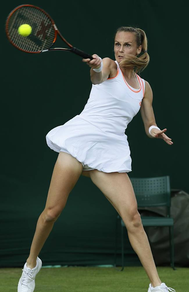 Magdalena Rybarikova of Slovakia plays a return to Belinda Bencic of Switzerland during their first round match at the All England Lawn Tennis Championships in Wimbledon, London, Tuesday, June 24, 2014