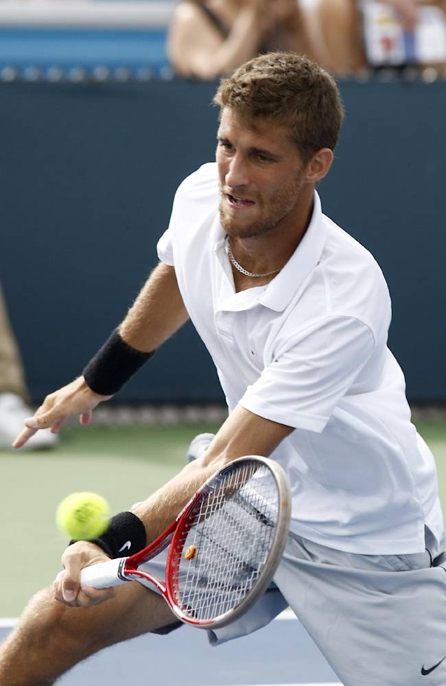 Martin Klizan, from Slovakia, returns to Roberto Bautista Agut, from Spain, during a first round match at the Western & Southern Open tennis tournament, Tuesday, Aug. 12, 2014, in Mason, Ohio