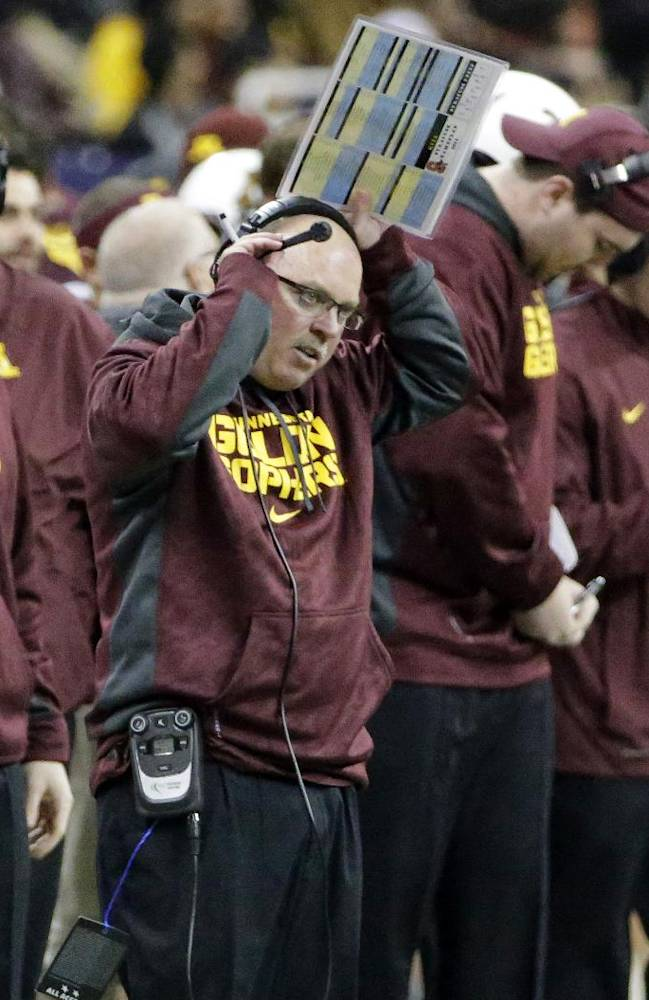 Minnesota coach Jerry Kill, center, adjusts his headset while coaching from the sideline during the third quarter of the Texas Bowl NCAA college football game against Syracuse, Friday, Dec. 27, 2013, in Houston. Syracuse won 21-17
