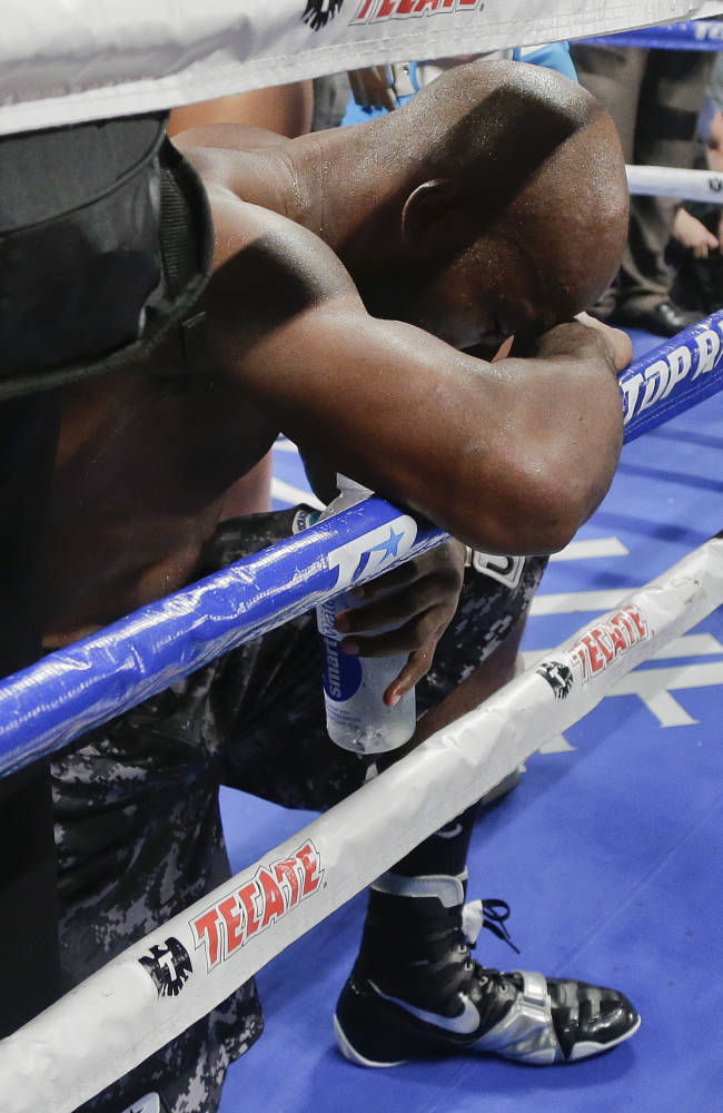Timothy Bradley kneels and bows his head on the ropes after defeating Juan Manuel Marquez by split decision during a WBO welterweight title fight, Saturday, Oct. 12, 2013, in Las Vegas