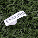 A discarded label bearing the name of Steve Sarkisian, former Washington head football coach, rests on the turf Saturday, April 19, 2014, during Washington's spring NCAA college football preview in Seattle under the direction of coach Chris Petersen. Sark