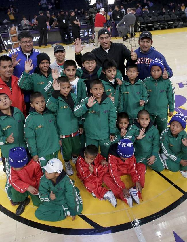 Members of Triqui kids basketball team, made up of children from the mountainous region of Oaxaca, Mexico, pose for a pictures at half court before an NBA basketball game between the Los Angeles Lakers and the Minnesota Timberwolves in Los Angeles, Friday, Dec. 20, 2013