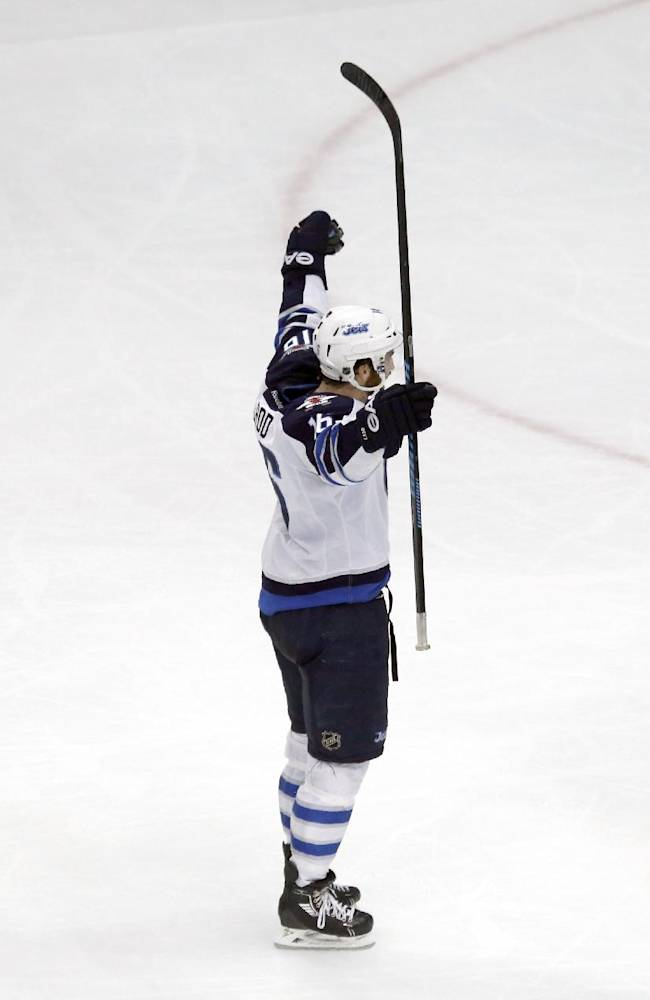 Winnipeg Jets left wing Andrew Ladd, center, celebrates his goal with defenseman Tobias Enstrom, left, and Michael Frolik during the third period of an NHL hockey game, Sunday, Jan. 26, 2014, in Chicago. The Jets won 3-1