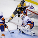 Boston Bruins center Patrice Bergeron (37) turns the corner to score a goal against New York Islanders goalie Kevin Poulin (60) while Islanders center John Tavares (91) and defenseman Matt Donovan (46) try to defend in the first period of an NHL preseason