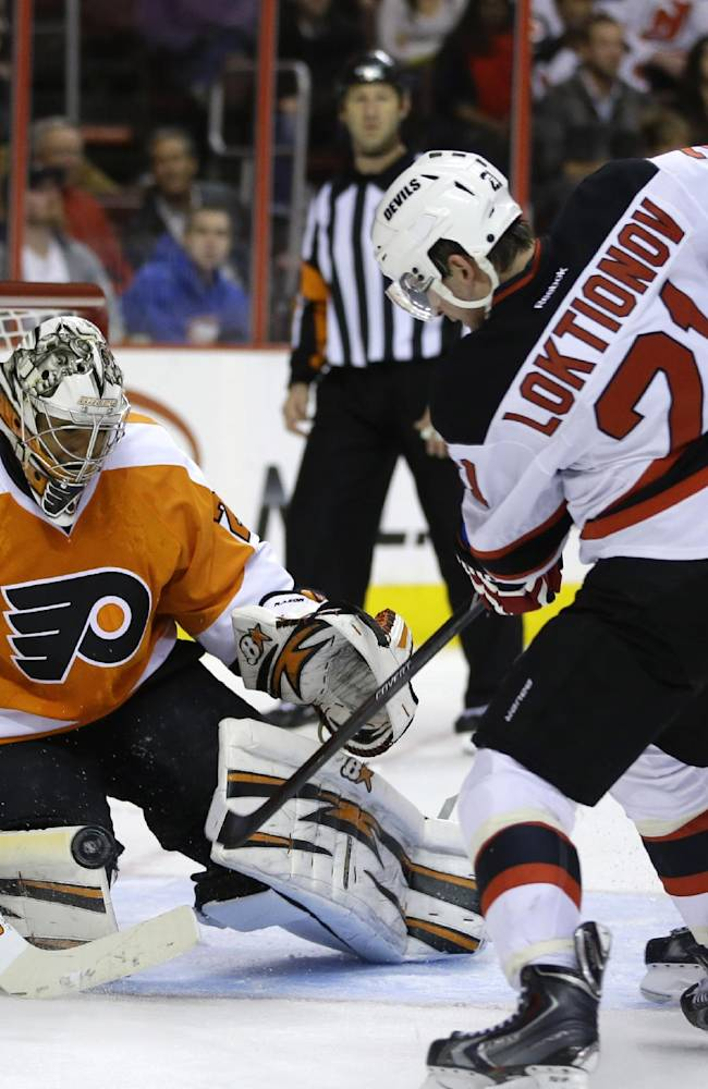New Jersey Devils' Andrei Loktionov (21), of Russia, tries to get a shot past Philadelphia Flyers' Ray Emery (29) as Flyers' Kimmo Timonen (44), of Finland, defends during the third period of an NHL hockey game on Thursday, Nov. 7, 2013, in Philadelphia. New Jersey won 3-0