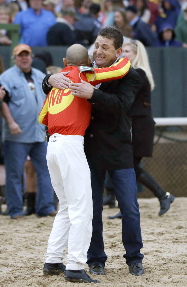Assistant trainer Jimmy Barnes, right, hugs jockey Mike Smith after Smith rode Hoppertunity to victory in the $600,000 Rebel Stakes horse race at Oaklawn Park in Hot Springs, Ark., Saturday, March 15, 2014