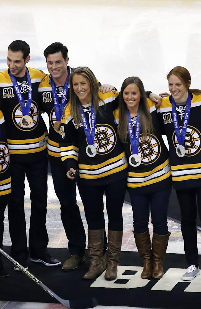Boston Bruins center Patrice Bergeron (37) greets New England athletes who medaled in the 2014 Olympic Winter Games in Sochi as they are honored prior to an NHL hockey game between the Bruins and the Florida Panthers in Boston, Tuesday, March 4, 2014. From left are Alex Deibold, Marissa Castelli, Simon Shnapir, Steve Langton, Meghan Duggan, Kelli Stack, Molly Schaus, Alex Carpenter, Michelle Picard and Kacey Bellamy