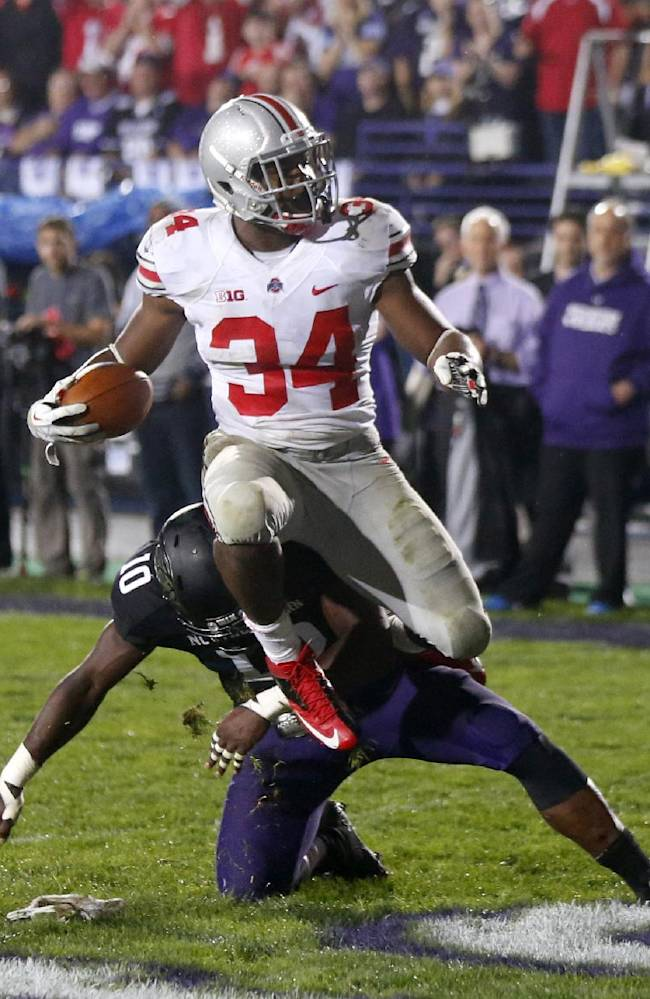 In this Oct. 5, 2013 file photo, Ohio State running back Carlos Hyde, top, scores over Northwestern safety Traveon Henry during the second half of an NCAA football game in Evanston, Ill.  Ohio State coach Urban Meyer says he encounters the question all the time: Why have you never had a tailback rush for 1,000 yards? He's tired of hearing it because he is totally committed to running the ball with a quality back