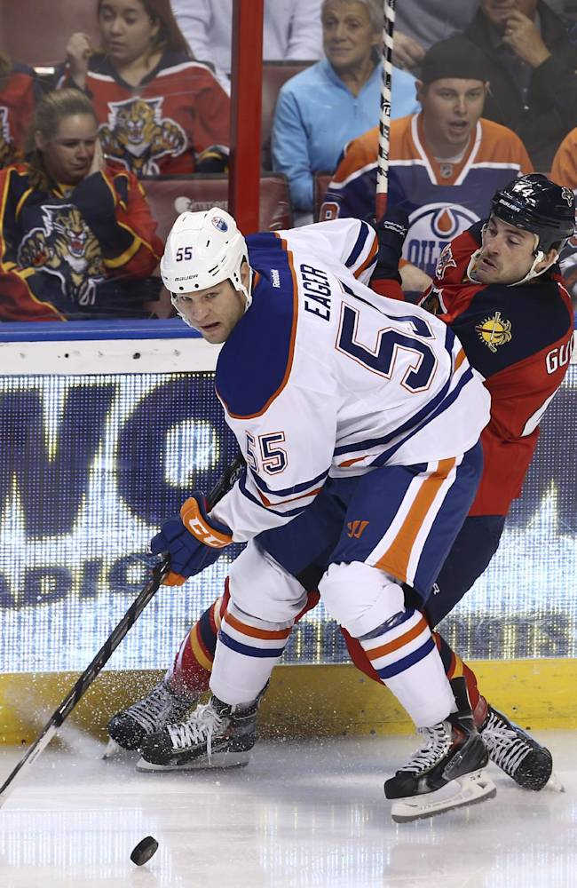 Edmonton Oilers' Ben Eager (55) and Florida Panthers' Erik Gudbranson (44) battle for the puck during the first period of an NHL hockey game in Sunrise, Fla., Tuesday, Nov. 5, 2013. (AP J Pat Carter)