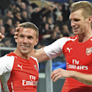 Arsenal's Per Mertesacker congratulates teammate and fellow countryman Lukas Podolski, after Podolski decided the match scoring 2-1 during the Group D Champions League match between Anderlecht and Arsenal at Constant Vanden Stock Stadium in Brussels, Belg