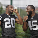 Oakland Raiders players Darren McFadden, left, jokes with his teammate Marcel Reece, right, as they watch children playing football during an event at Guildford, England, Tuesday, Sept. 23, 2014. The Raiders will play the Miami Dolphins in an NFL football