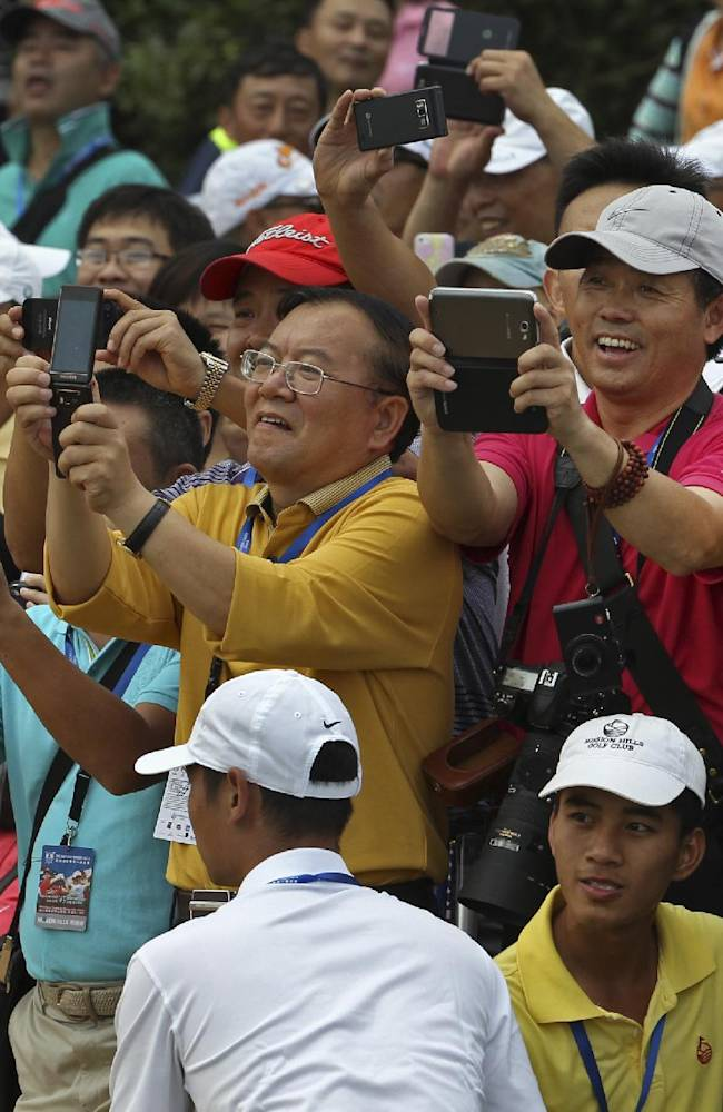 Chinese golf fans watch Tiger Woods of the United States and Rory Mcllory of Northern Ireland playing during an exhibition golf match in Haikou, in southern China's island province Hainan, Monday, Oct. 28, 2013. Mcllory won the tournament, finishing on 6-under 73