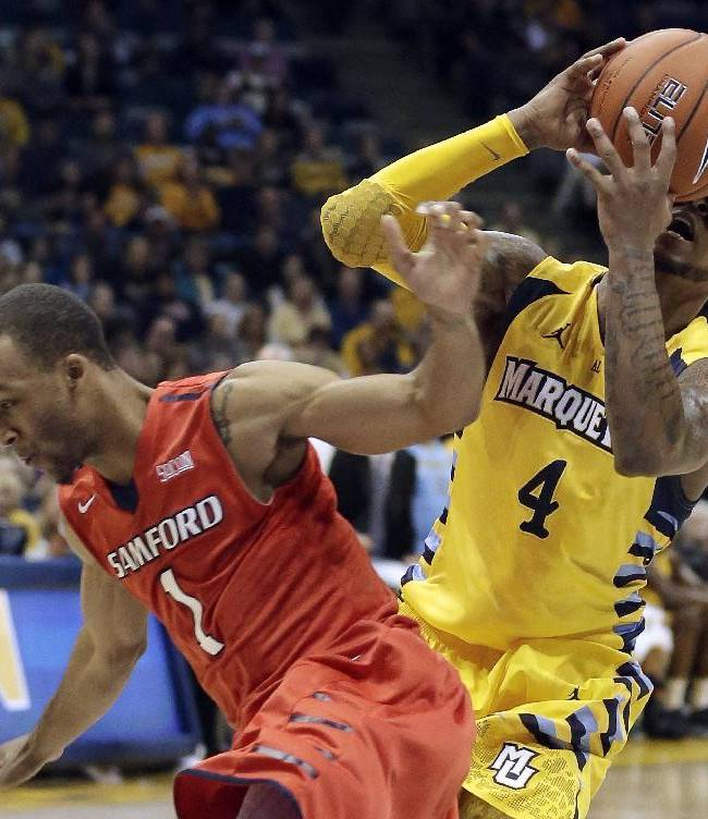 Marquette's Todd Mayo loses the ball as he is fouled by Samford's Brandon Roberts (1) during the first half of an NCAA college basketball game Saturday, Dec. 28, 2013, in Milwaukee