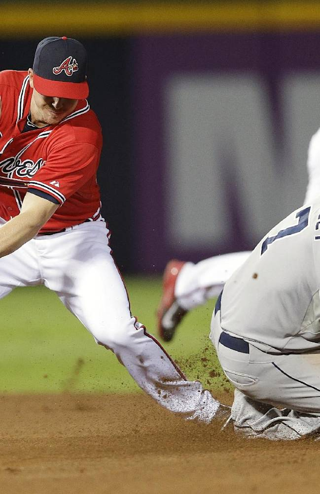 San Diego Padres' Chase Headley (7) steals second base as the ball gets away from Atlanta Braves second baseman Elliot Johnson in the fourth inning of a baseball game in Atlanta, Friday, Sept. 13, 2013