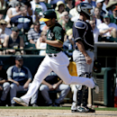 Oakland Athletics' Sam Fulg, left, scores past Seattle Mariners catcher John Buck on a bunt by Eric Sogard during the second inning of a spring exhibition baseball game in Phoenix, Saturday, March 22, 2014 The Associated Press