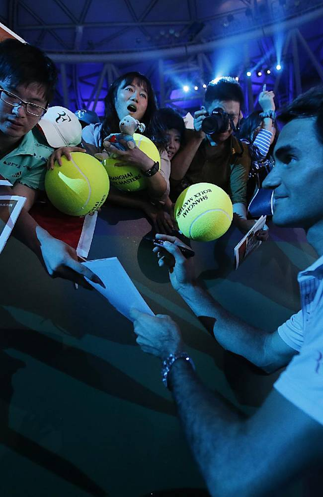Roger Federer of Switzerland gives his autographs to fans during a fan meeting event ahead of the Shanghai Masters at Qizhon Tennis Center in Shanghai, China, Saturday, Oct. 5, 2013