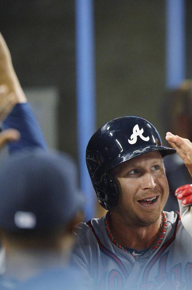 Atlanta Braves' Elliot Johnson is greeted in the dugout after he scored in the seventh inning of Game 4 in the National League baseball division series against the Los Angeles Dodgers, Monday, Oct. 7, 2013, in Los Angeles