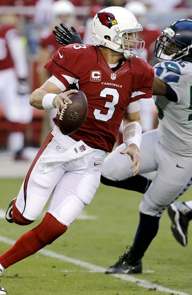 Arizona Cardinals quarterback Carson Palmer (3) scrambles under pressure from Seattle Seahawks defensive end Cliff Avril (56) during the first half of an NFL football game, Thursday, Oct. 17, 2013, in Glendale, Ariz