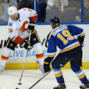 Calgary Flames' Brian McGrattan (16) looks to pass around St. Louis Blues' Jay Bouwmeester (19) during the third period of an NHL hockey game, Saturday, Oct. 11, 2014, in St. Louis The Associated Press