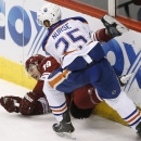 Edmonton Oilers' Darnell Nurse (25) checks Arizona Coyotes' Shane Doan into the boards during the third period of an NHL hockey game Wednesday, Oct. 15, 2014, in Glendale, Ariz. The Coyotes defeated the Oilers 7-4 The Associated Press