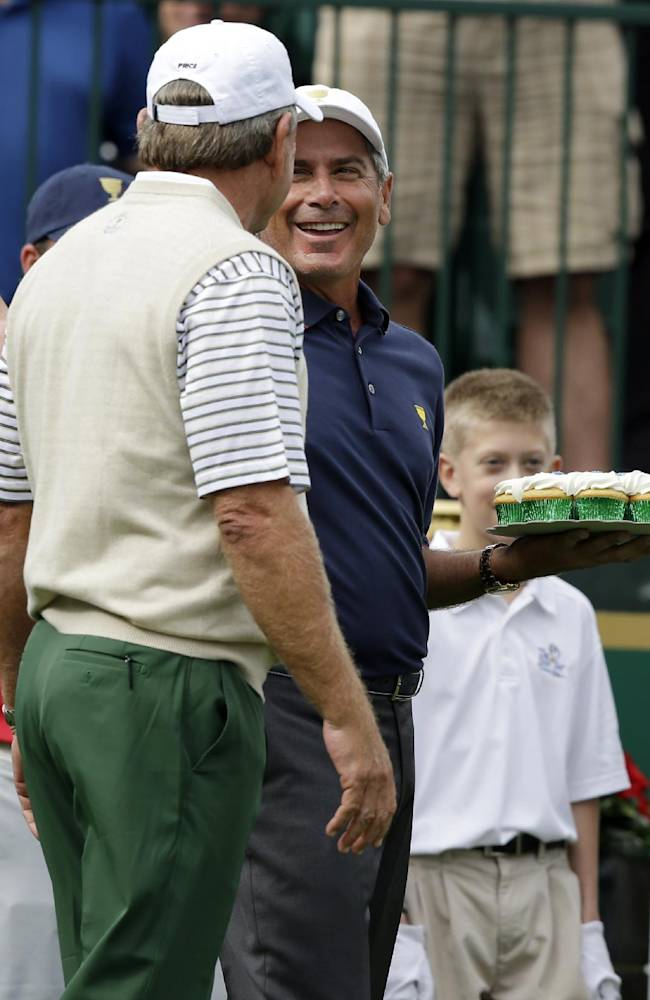 United States captain Fred Couples, right, laughs after being presented with cupcakes for his birthday from International captain Nick Price before the start of the four-ball matches at the Presidents Cup golf tournament at Muirfield Village Golf Club Thursday, Oct. 3, 2013, in Dublin, Ohio