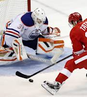 Detroit Red Wings' Tomas Tatar (21), of the Czech Republic, drives in on Edmonton Oilers' Viktor Fasth (35), of Sweden, to score the only goal in a shootout to defeat the Oilers 2-1 in an NHL hockey game on Friday, March 14, 2014, in Detroit. (AP Photo/Duane Burleson)