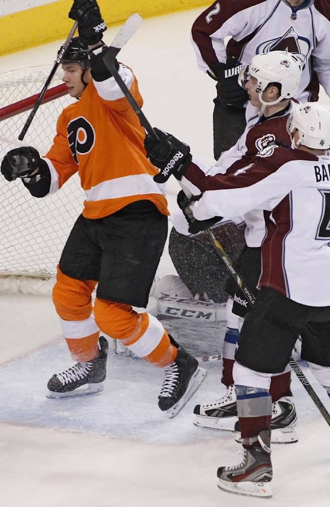 Philadelphia Flyers' Michael Raffl, left, raises his stick to celebrate his goal during the third period of an NHL hockey game in front of Colorado Avalanche players Matt Duchene, center, and Tyson Barrie, right, Thursday, Feb. 6, 2014, in Philadelphia. The Flyers won 3-1