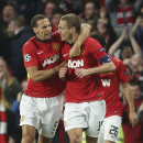Manchester United's Rio Ferdinand, left, congratulates Nemanja Vidic after scoring the opening goal during the Champions League quarterfinal first leg soccer match between Manchester United and Bayern Munich at Old Trafford Stadium, Manchester, England, T