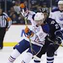 Edmonton Oilers forward Ryan Nugent-Hopkins (93) drives past Winnipeg Jets forward TJ Galiardi (21) during the second period of an NHL preseason hockey game Wednesday, Sept. 24, 2014, in Winnipeg, Manitoba. The Associated Press