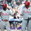 Philadelphia Phillies' Jimmy Rollins, left, applauds after scoring on a double by Ryan Howard as teammate Marlon Byrd heads to the plate to bat against the Colorado Rockies in the seventh inning of the Phillies' 10-9 victory in a baseball game in Denver o