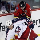 Columbus Blue Jackets' James Wisniewski, left, falls on the stick of Calgary Flames' Lee Stempniak during first period NHL hockey action in Calgary, Alberta, Wednesday, Nov. 20, 2013 The Associated Press