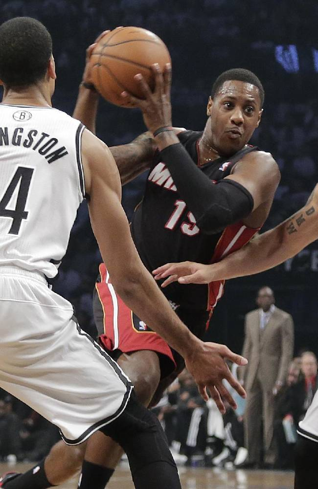 Miami Heat guard Mario Chalmers (15) drives against Brooklyn Nets guards Shaun Livingston (14) and Deron Williams (8) in the second period during Game 3 of an Eastern Conference semifinal NBA playoff basketball game on Saturday, May 10, 2014, in New York