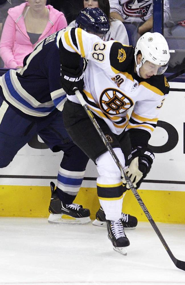 Boston Bruins' Jordan Caron, right, carries the puck away from Columbus Blue Jackets' James Wisniewski during the third period of an NHL hockey game Saturday, Oct. 12, 2013, in Columbus, Ohio. The Bruins beat the Blue Jackets 3-1