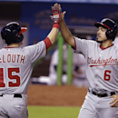Washington Nationals' Nate McLouth (15) greets Anthony Rendon (6) at the plate after they scored on a single by Ian Desmond during the eighth inning of a baseball game against the Miami Marlins, Wednesday, April 16, 2014, in Miami. The Nationals defeated
