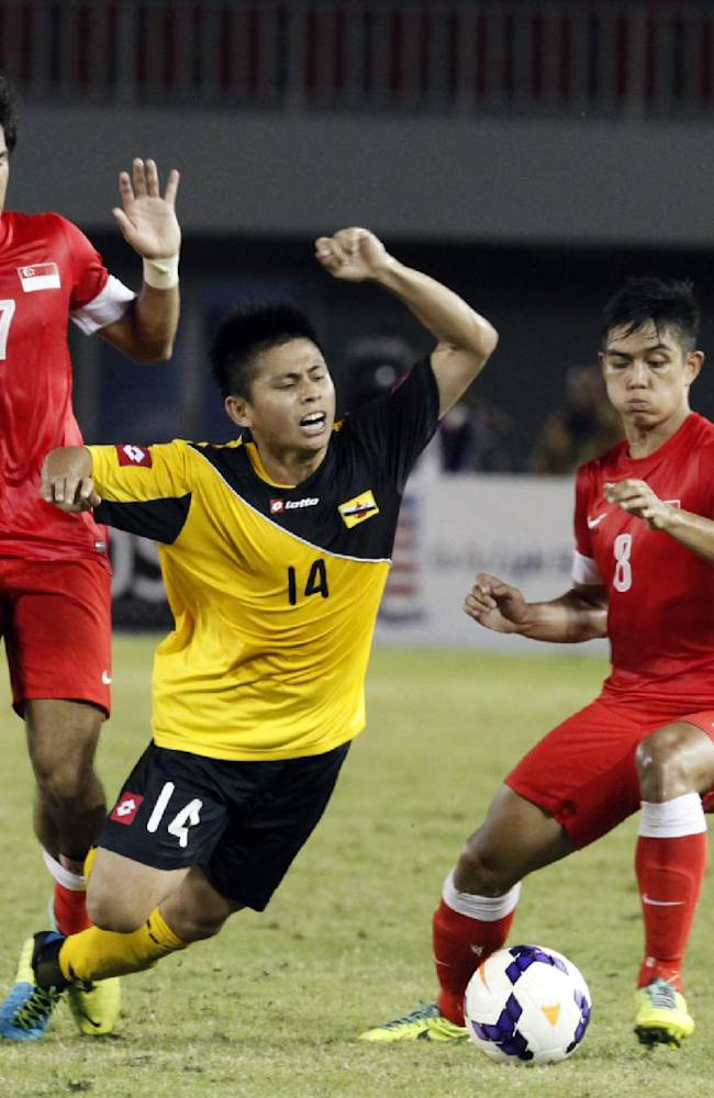 Mohd Akmal Hakeen And Hamid of Brunei, center, falls as he vies for the ball against two Singapore players, Muhammad Hafis Abu Sujad, right, and Muhammad Zulfahmi Mohd Arifin, during their soccer match at the 27th SEA Games in Naypyitaw, Myanmar, Friday, Dec. 13, 2013. Singapore beat Brunei with 2-0