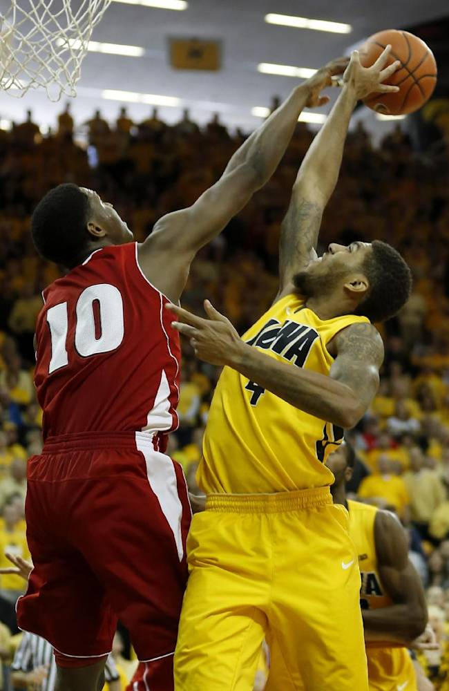 Iowa guard Devyn Marble has his shot blocked by Wisconsin forward Nigel Hayes during the second half of an NCAA college basketball game in Iowa City, Iowa, Saturday, Feb. 22, 2014. Wisconsin won 79-74