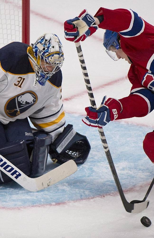 Buffalo Sabres' goaltender Matt Hackett, left, keeps an eye on the puck as Montreal Canadiens' Michael McCarron moves in during third period NHL pre-season hockey action in Montreal, Sunday, Sept. 15, 2013