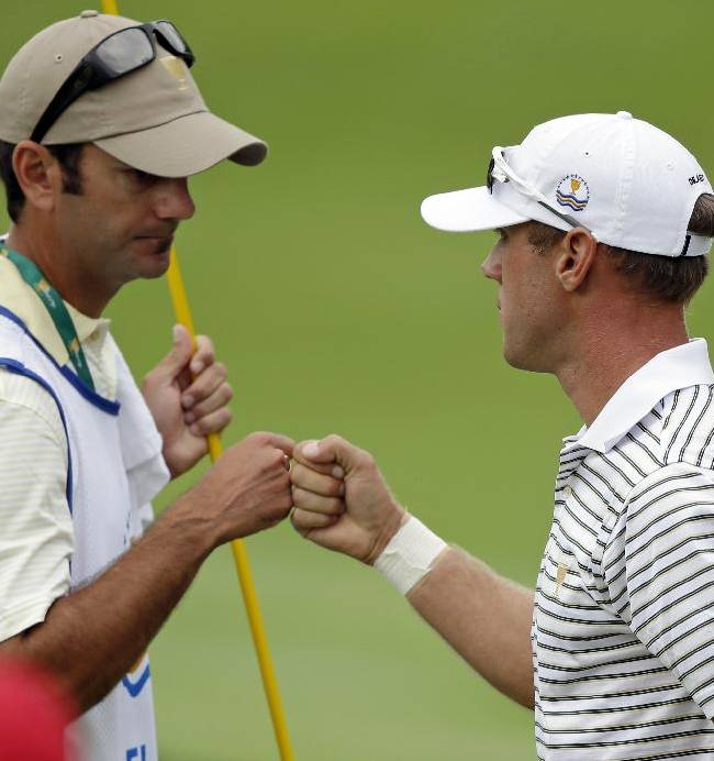 International team player Graham DeLaet, right, of Canada, bumps fists with his caddie Julien Trudeau after making birdie on the first hole during a four-ball match against the United States at the Presidents Cup golf tournament at Muirfield Village Golf Club Thursday, Oct. 3, 2013, in Dublin, Ohio