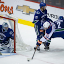Edmonton Oilers' Anton Lander (51), of Sweden, is checked by Vancouver Canucks' Nick Bonino (13) and Dan Hamhuis (2) as he attempts a shot on goalie Ryan Miller during the third period of an NHL hockey preseason game Saturday, Oct. 4, 2014, in Vancouver,