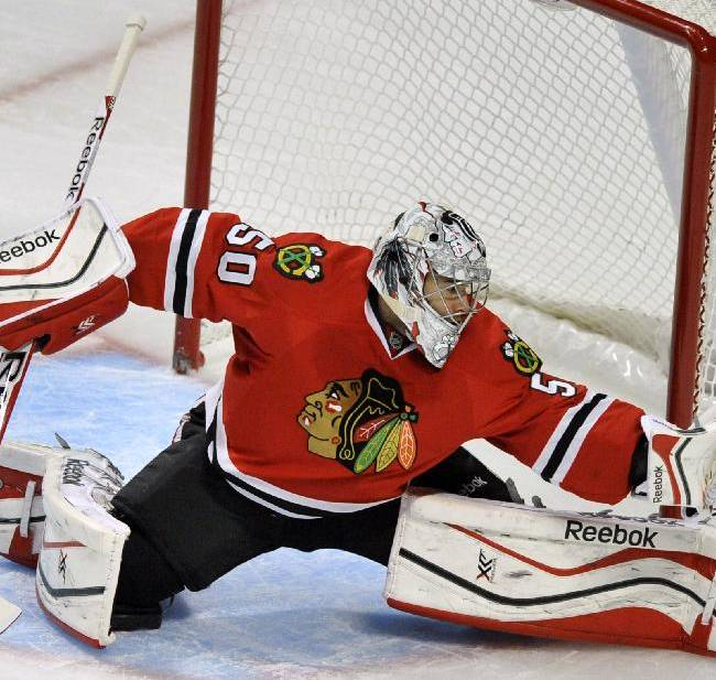 Chicago Blackhawks goalie Corey Crawford makes a save during the first period of an NHL hockey game against the Calgary Flames in Chicago, Sunday, Nov. 3, 2013