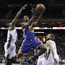 Golden State Warriors' Harrison Barnes, center, drives between Charlotte Bobcats' Anthony Tolliver, left, and Josh McRoberts, right, during the first half of an NBA basketball game in Charlotte, N.C., Monday, Dec. 9, 2013 The Associated Press