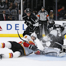 Calgary Flames right wing David Jones, center, falls to the ice as he attempts a shot against Los Angeles Kings goalie Jonathan Quick, right, while Kings defenseman Robyn Regehr, rear center, Kings center Jarret Stoll, left, also defend during the third p
