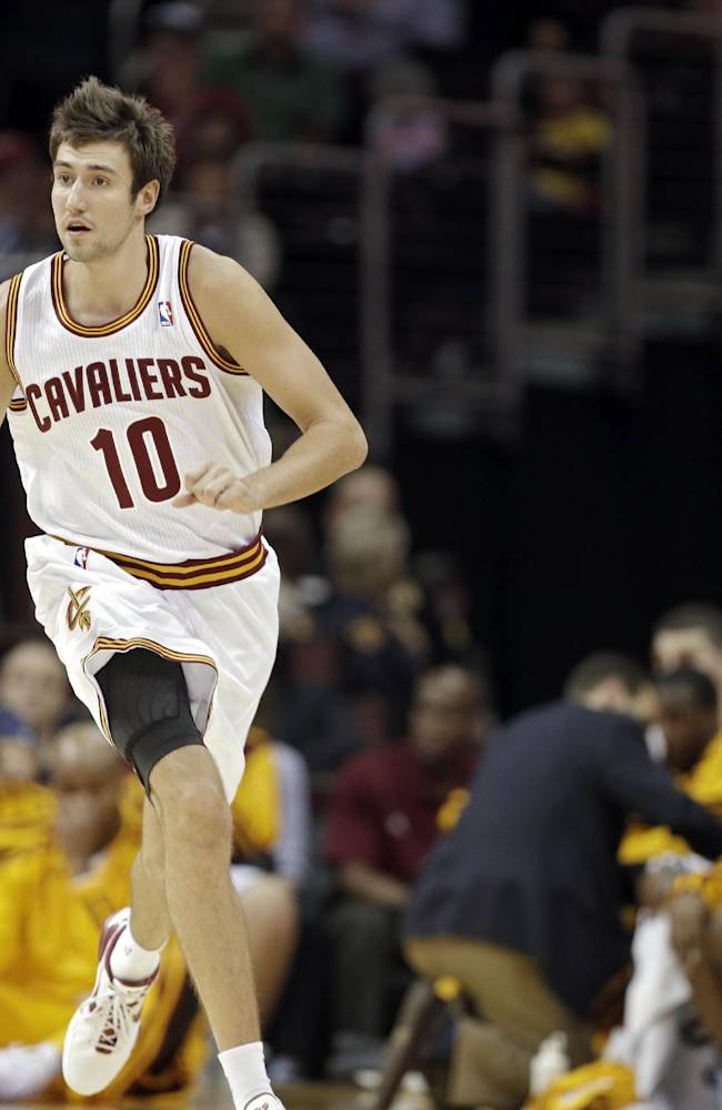 Cleveland Cavaliers' Sergey Karasev (10), of Russia, dribbles he ball as the Indiana Pacers as head coach Mike Brown gestures, right, in the first quarter of a preseason NBA basketball game Saturday, Oct. 19, 2013, in Cleveland