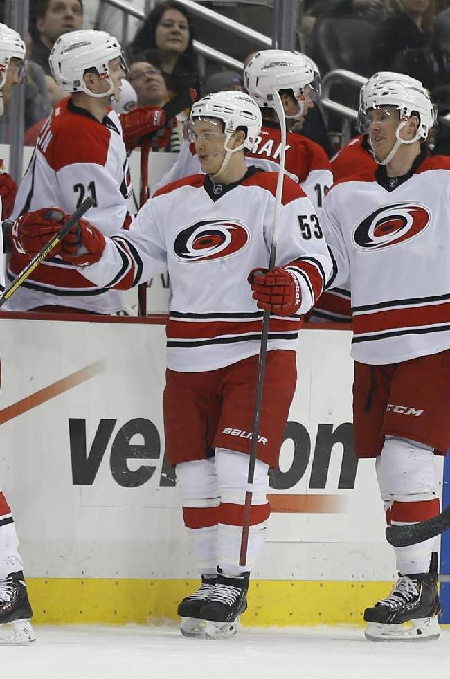 Carolina Hurricanes' Elias Lindholm (16), of Sweden, leads his linemates past the bench as they celebrate his second goal of the second period of an NHL hockey game against the Pittsburgh PenguinsonTuesday, April 1, 2014, in Pittsburgh
