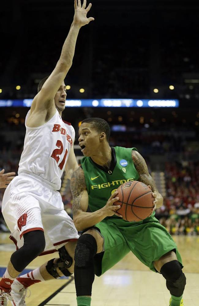 Oregon guard Joseph Young drives the ball against Wisconsin guard Josh Gasser (21) during the first half of a third-round game of the NCAA college basketball tournament Saturday, March 22, 2014, in Milwaukee