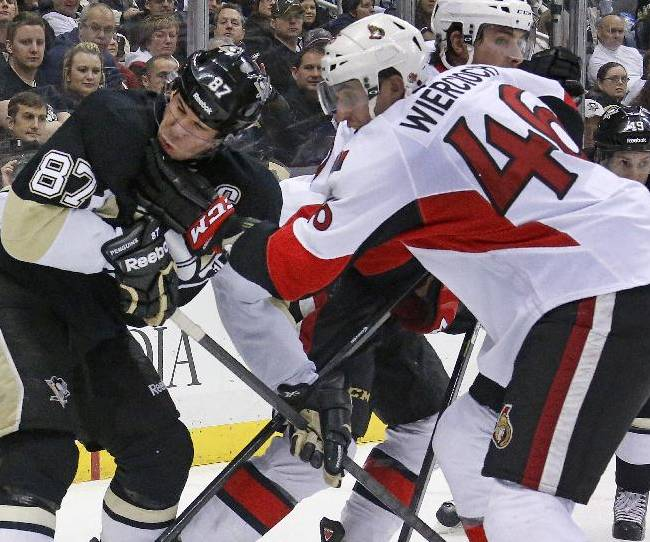 Ottawa Senators' Patrick Wiercioch (46) gets his glove in the face of Pittsburgh Penguins' Sidney Crosby (87) in the second period of an NHL hockey game in Pittsburgh, Monday, Feb. 3, 2014