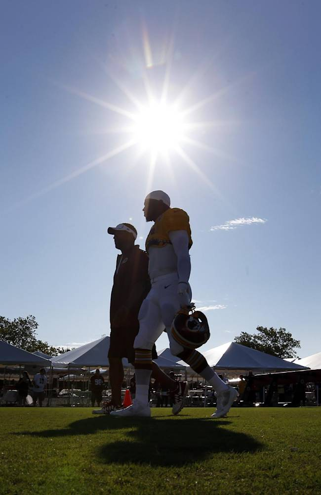 Washington Redskins quarterback Robert Griffin III, right, walks to the field for practice at the team's NFL football training facility, Monday, July 28, 2014 in Richmond, Va