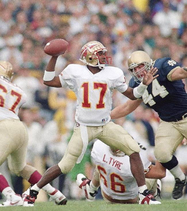 In this Nov. 13, 1993, file photo, Florida State quarterback Charlie Ward looks for a receiver as Notre Dame tackle Jim Flanigan (44) bears down on Ward during the first quarter, Nov. 13, 1993 in South Bend, Indiana. Two decades later, it's still open to debate whether college football ever had a better afternoon than on Nov. 13, 1993, when No. 1 Florida State visited No. 2 Notre Dame