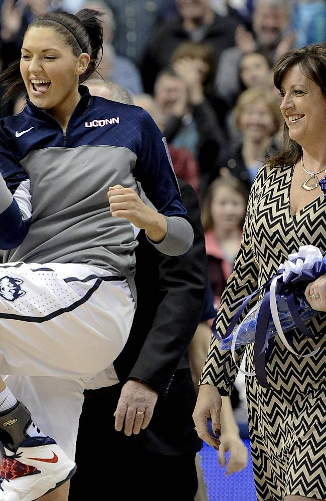 Connecticut's Stefanie Dolson, left, dances as she is escorted to the court by her mother Krystal, right, as Dolson is honored at senior night before an NCAA college basketball game against Rutgers, Saturday, March 1, 2014, in Storrs, Conn